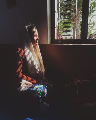 A Nepalese lady sits on the floor next to a window, the morning light casts shadows across her face.