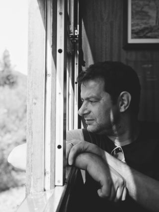 A man sat down looking out of the train window.