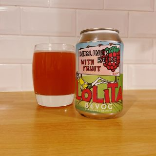 A can of raspberry ale alongside a glass containing a red beer