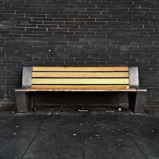 An empty wooden bench against a slate wall