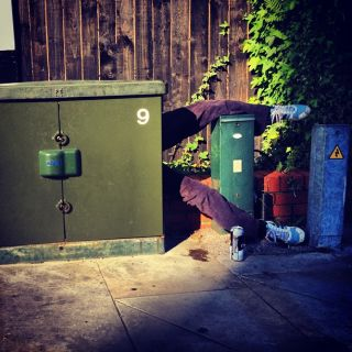 A pair of legs sticking out from behind an electricity cabinet with a can of beer on the floor