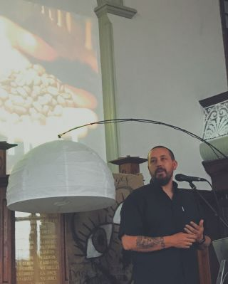 A man speaking into a microphone in a church