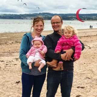 A family photo of a husband and wife holding two girls with the sea in the background.