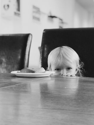 A little girls head at eye level of a table looking at the camera.