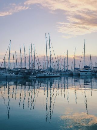 Reflections of boats in a mariener in the early morning light