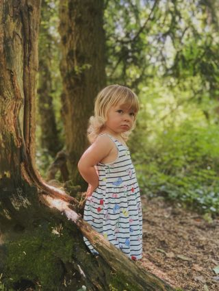 A little girl stands side on in dress and wellies in a wood