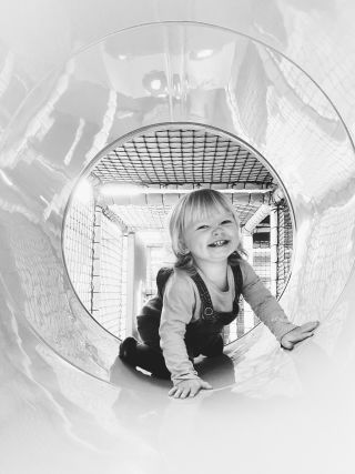 A little girl smiling in a soft play tunnel