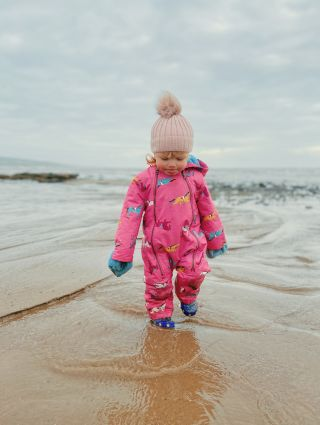 A little girl walking through the water on the beach wearing an all in one