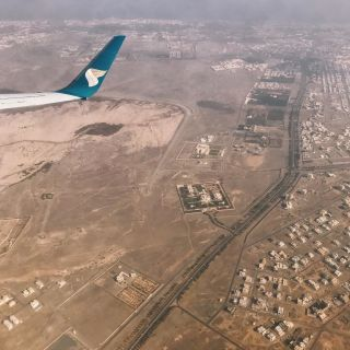 An aerial view of Oman from a plane showing buildings and large expanses of brown land