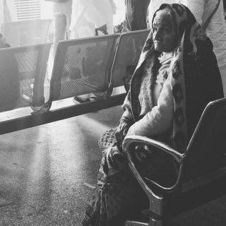 An old woman sitting in an airport chair in black and white