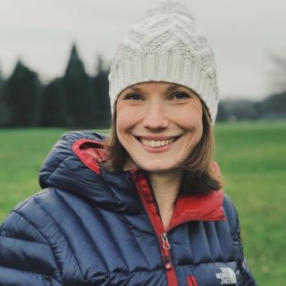 A woman smiling wearing a white bobble hat and a blue and red down jacket