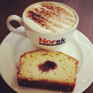 A cup of coffee and a slice of cake on a plate
