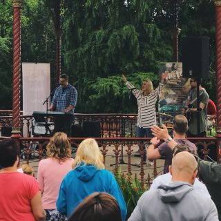 A young lady raises her arms in worship in a band stand