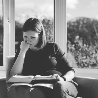 A woman sat reading a bible in a bay window