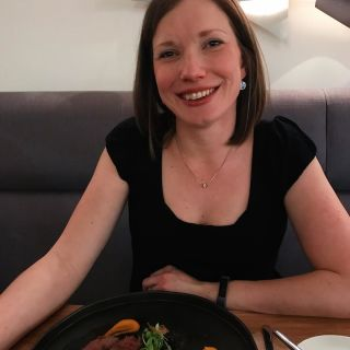 A woman sat at a restaurant table smiling