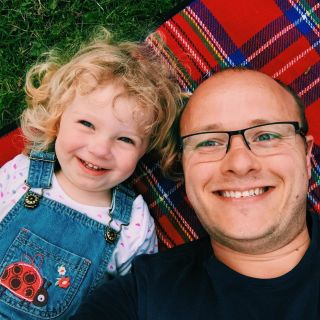 A child and her father laying on a picnic blanket