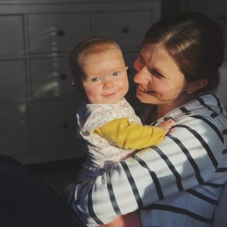 A mother in a stripy top holding a small baby