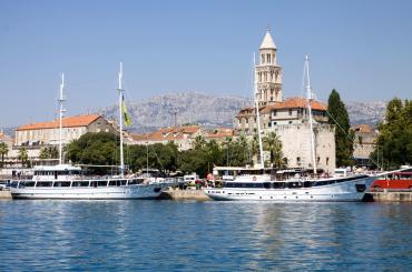 Ships tied along Split's promenade. Diocletian's palace and Cathedral & Bell Tower of St. Domnius behind them.