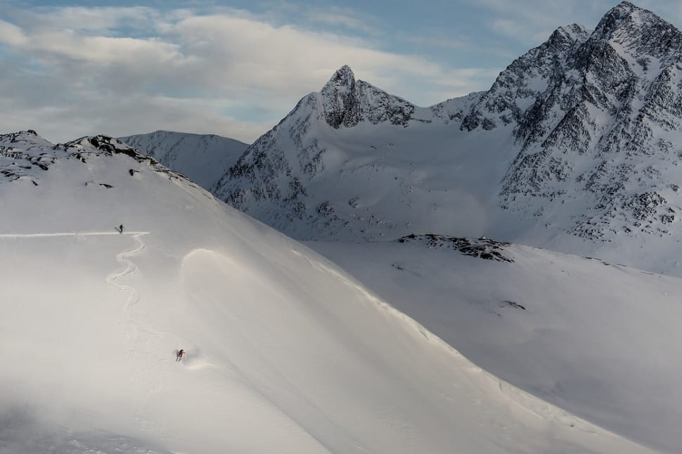 A skier carving a steep line near Kuummiut in East Greenland
