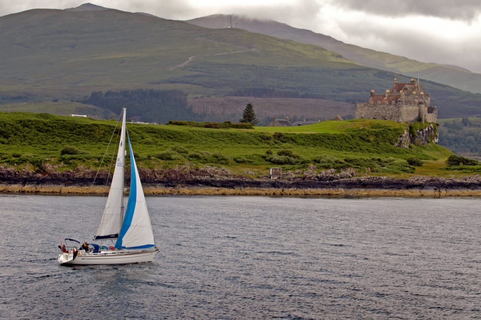 A yacht sailing in the Sound of Mull by Duart Castle on the Isle of Mull, Inner Hebrides