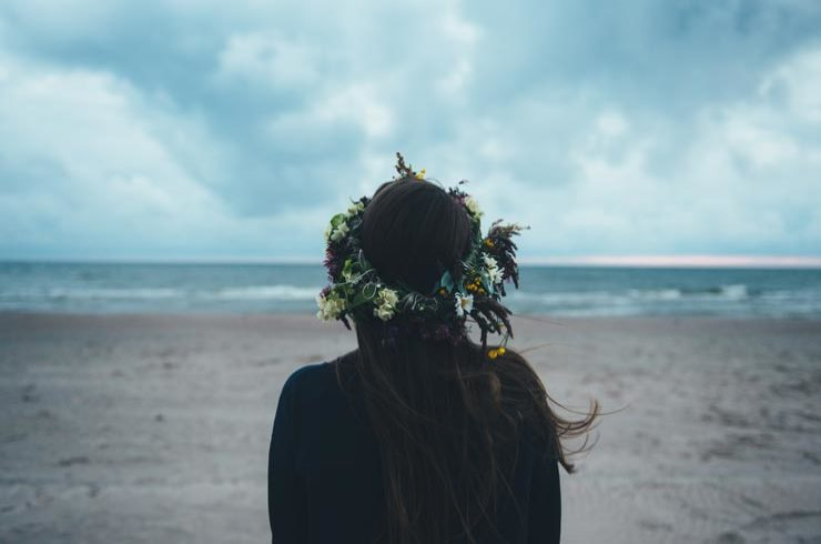 Girl wearing flower crown and looking at the sea