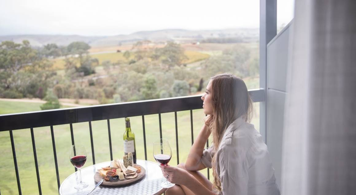woman sitting on balcony at novotel barossa with vineyards in the distance