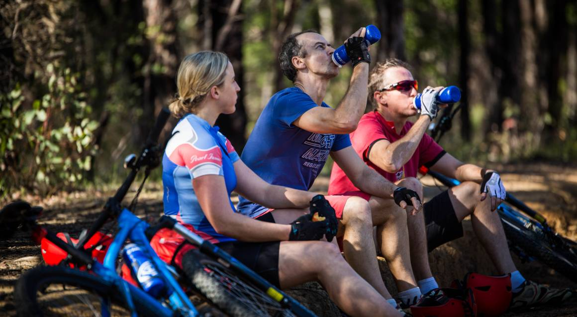 Mountain bike tour 3 people sitting down near mountain bikes in the bush 1 is drinking from a water bottle