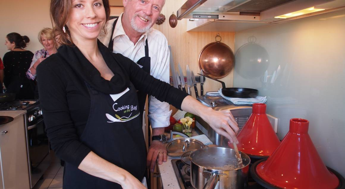 man and woman standing at an oven cooking on the hob