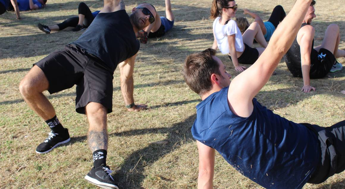 Commando steve doing side plank in outdoor group personal session in park
