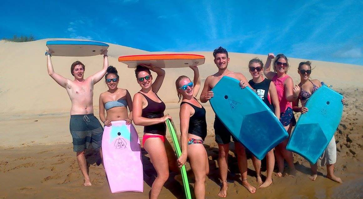 group of friends on the beach with surf boards