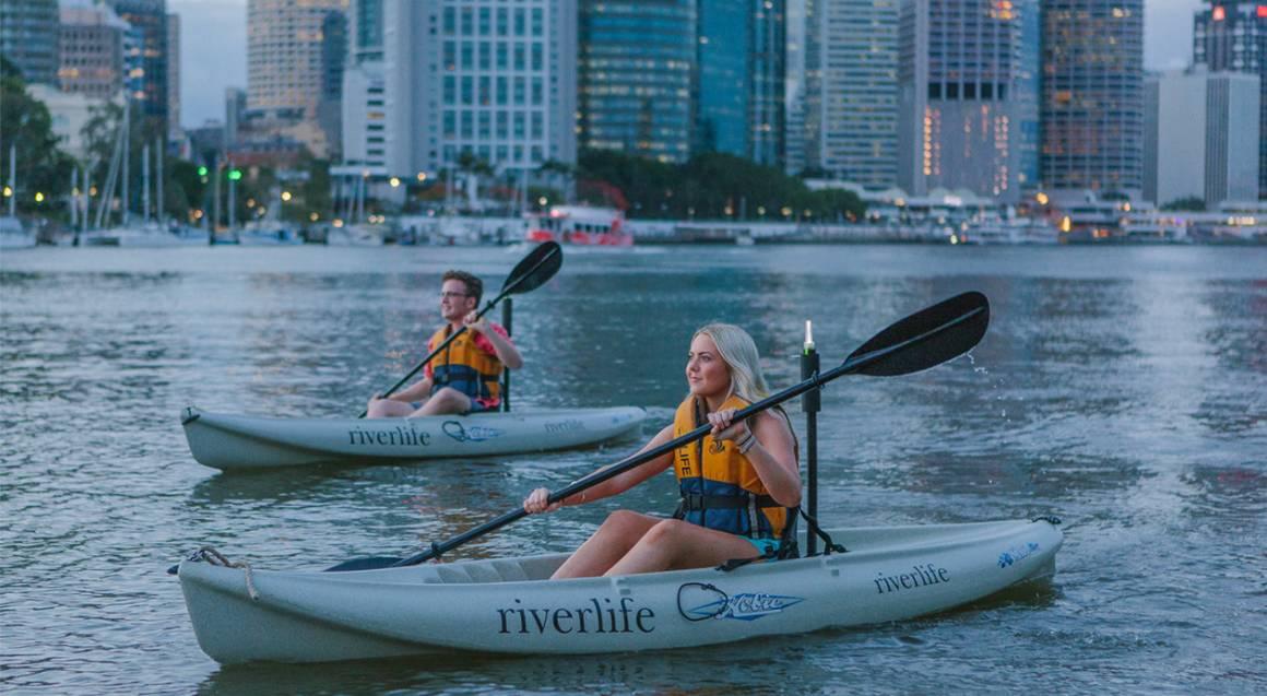 couple kayaking on brisbane river at sunset