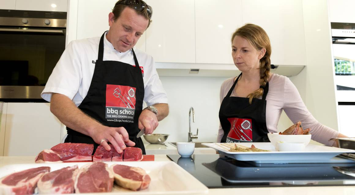 bbq cooking class man in apron showing woman in apron how to slice different cuts of raw meat in modern white