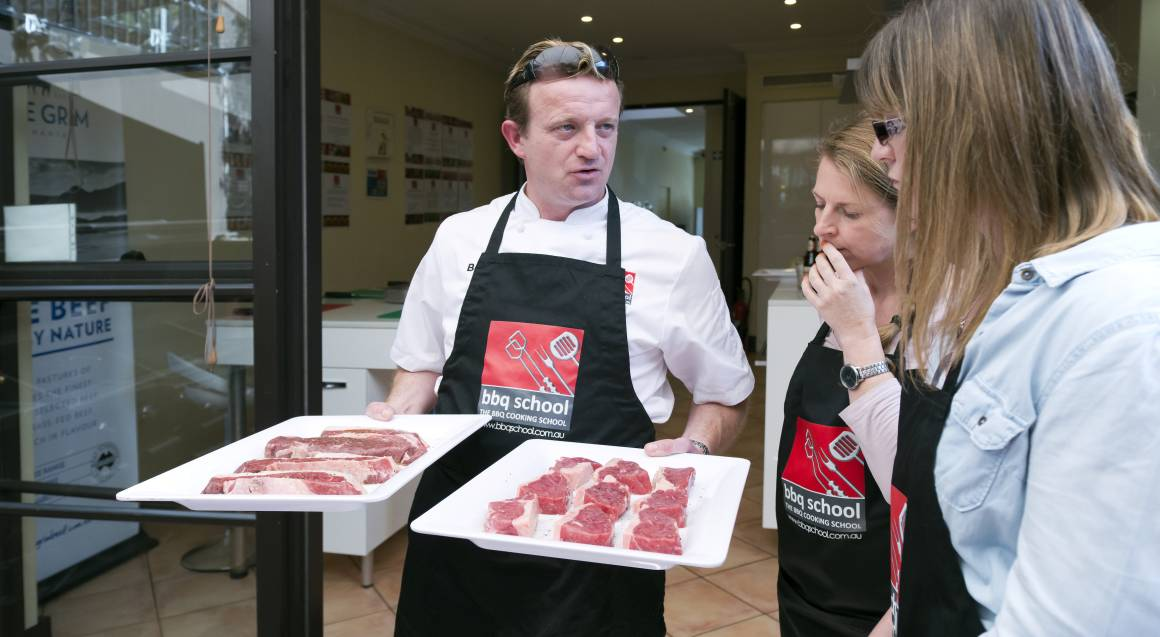 bbq cooking class man in apron bringing out 2 trays of raw meat from the kitchen in the background to the outside 2 woman in aprons are standing near him