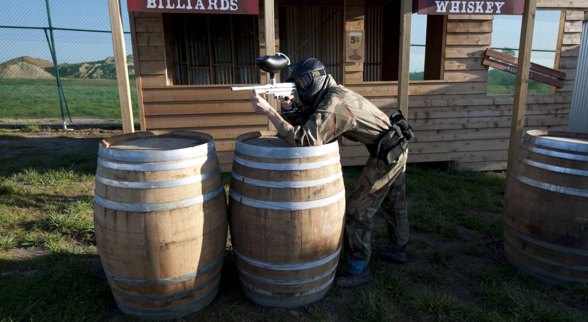 man playing paintball aiming gun on field