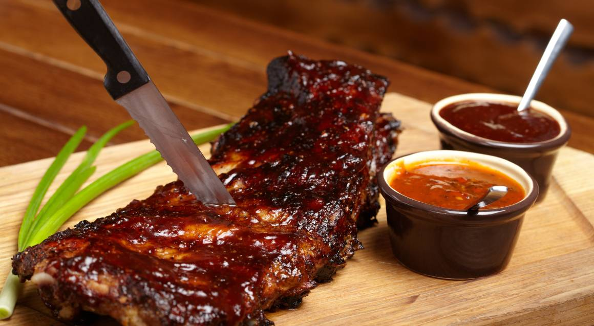 bbq cooking class rack of ribs basted in bbq sauce on wooden board with jars of sauce and knife stuck through them
