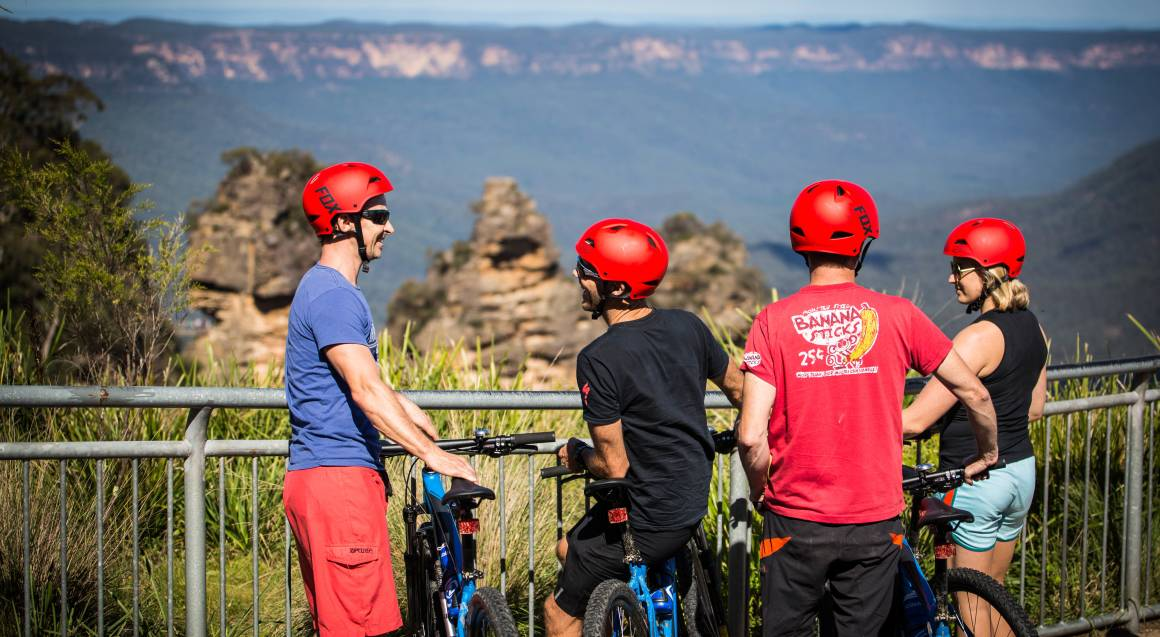 Mountain bike tour four people standing with mountain bikes and helmets on at a lookout railing with mountains and bushland that stretches off into the distance