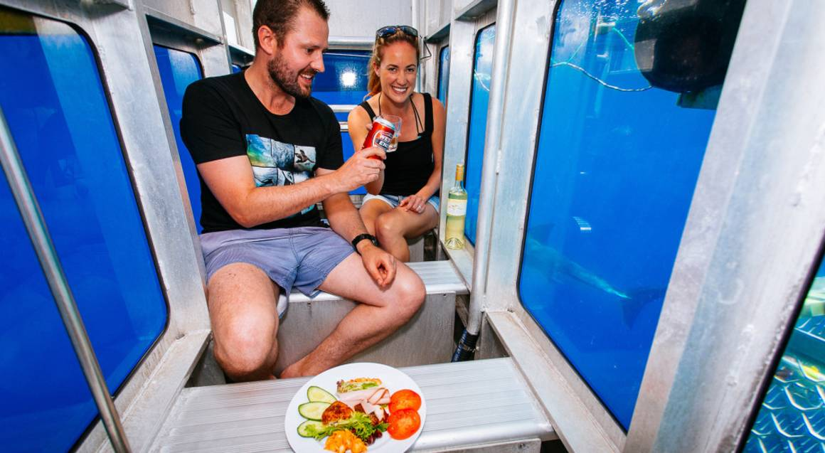 couple with lunch and wine in underwater viewing chamber