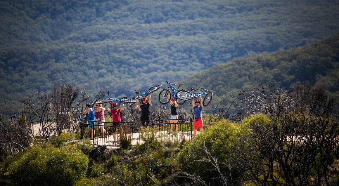 Mountain bike tour four people holding up mountain bikes above their heads with red helmets on at a lookout point bushland surrounds them