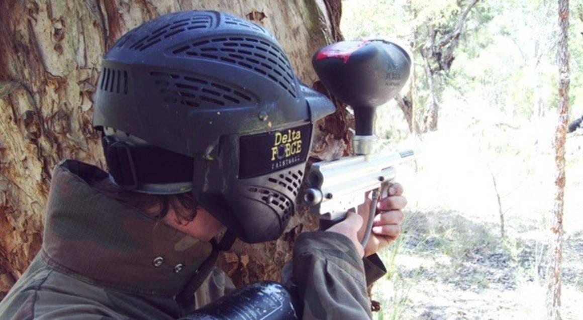 man playing paintball shooting gun from behind tree