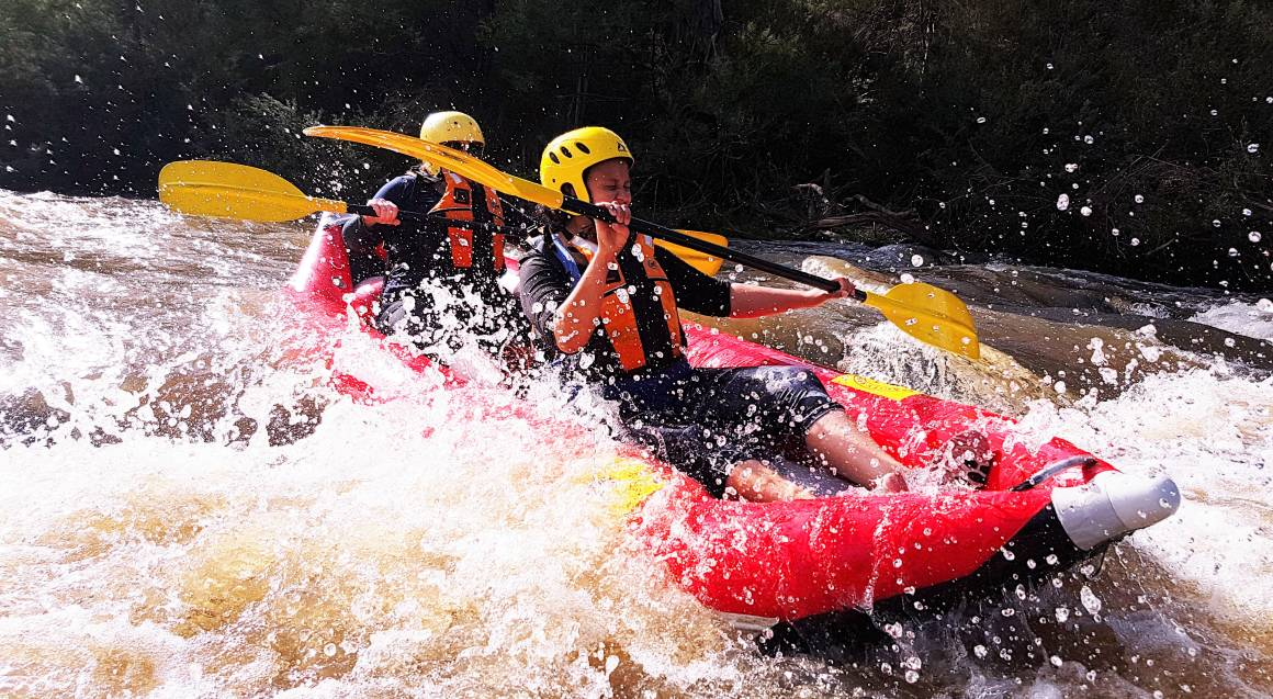 two people in a red raft paddling through white water rapids on yarra river