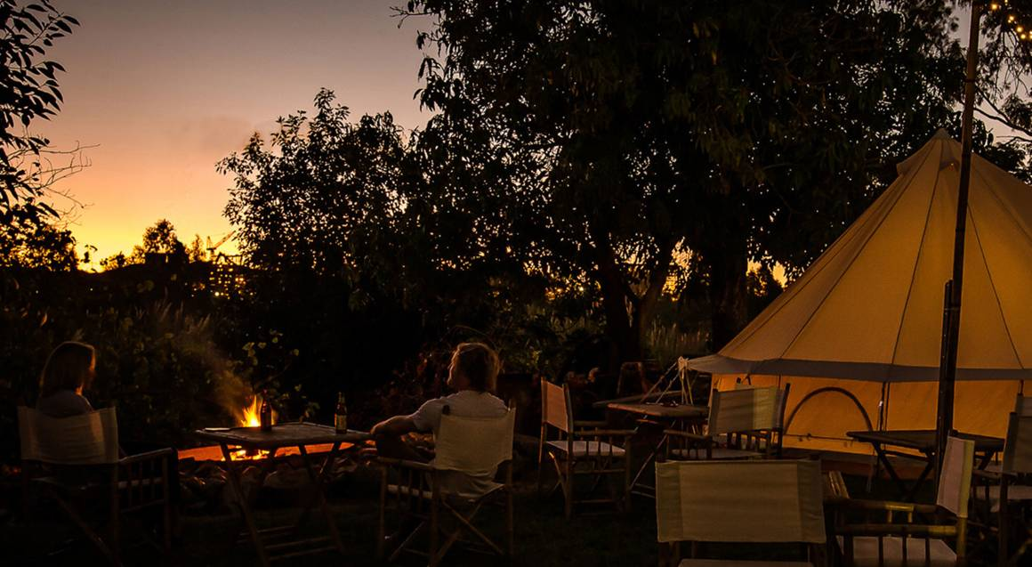 couple sitting outside glamping tent watching sunset