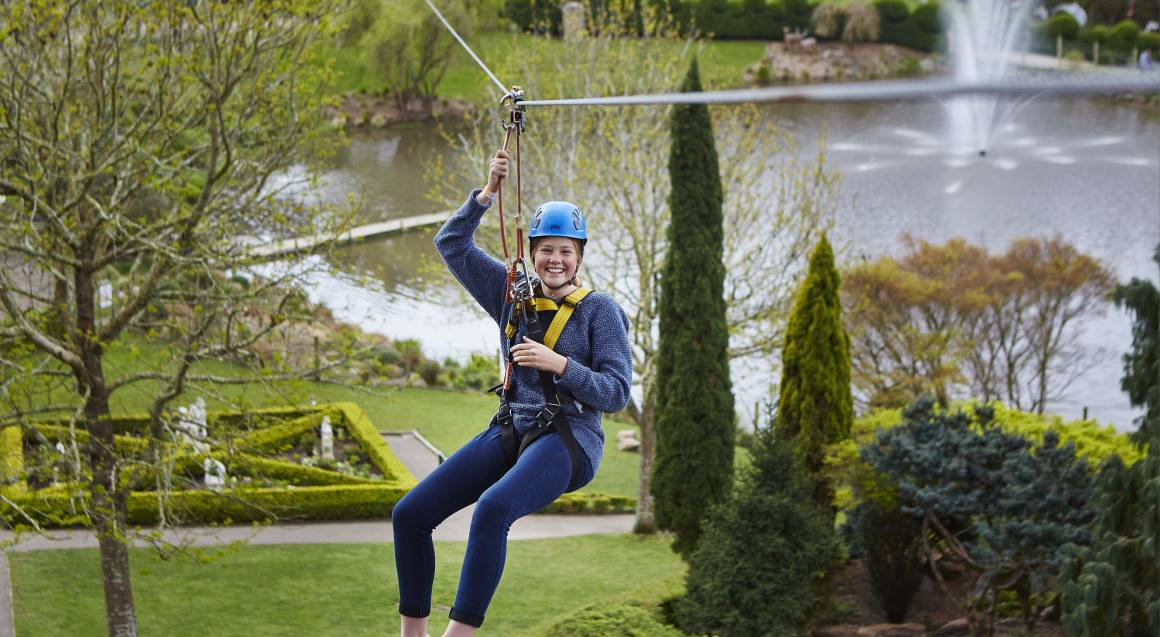 woman on zip wire above lake and garden