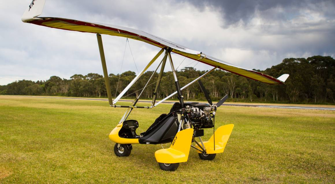 gyrocopter sitting on some grass with a cloudy sky in the background