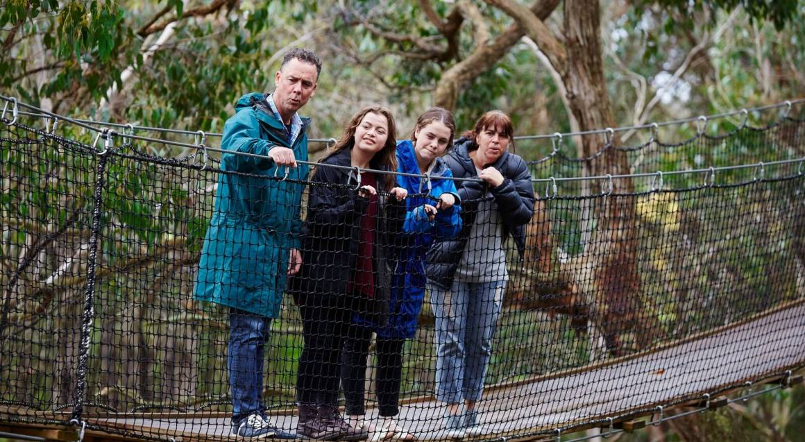 kids park group of parents and 2 teenage girls standing on a boardwalk with a net guard up among the trees