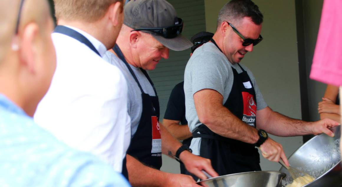 bbq cooking class 2 men in aprons in outdoor kitchen whisking food in big metal bowls