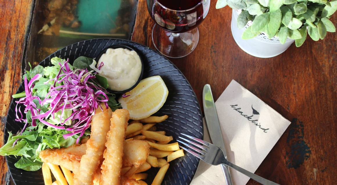 fish and chips with salad and glass of red wine