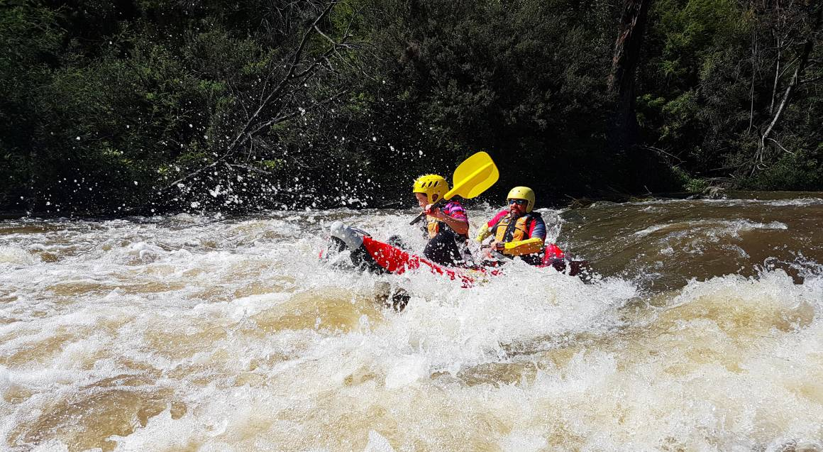 two people in a raft on white water rapids on yarra river