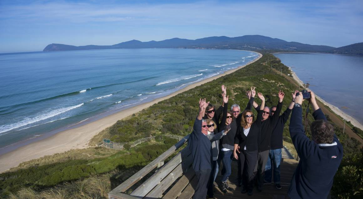 tour group posing for photo at a beach on bruny island