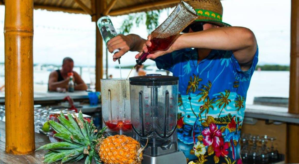 bartender making alcoholic fruit cocktail at beach bar