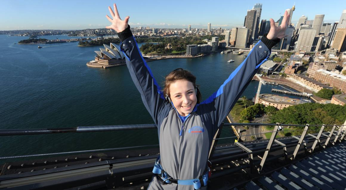 Cheerful girl climbing the Sydney Harbour Bridge with aerial view of Sydney in the background